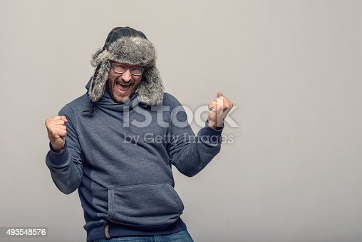 Happy man wearing glasses and a winter hat cheering and celebrating raising his clenched fists in the air with an exultant expression, over grey with copy space