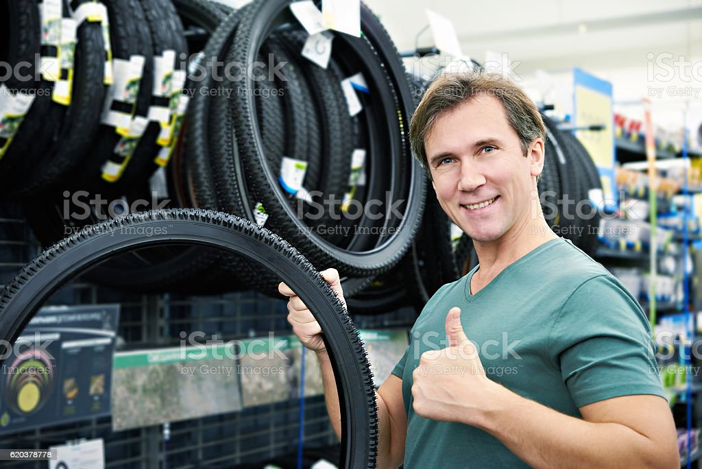 Happy man chooses tire to bike in sports shop zbiór zdjęć royalty-free