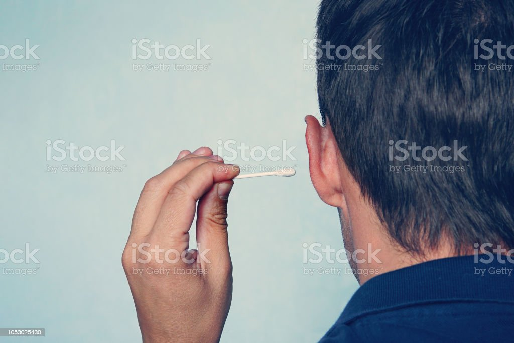 Happy man cleans his ear with a cotton swab close-up on blue background stock photo