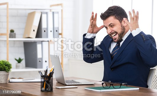 Happy man completed task and triumphing with raised hands, sitting at workplace in office, empty space