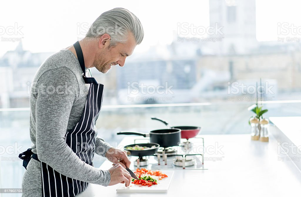 Happy man cooking at home stock photo