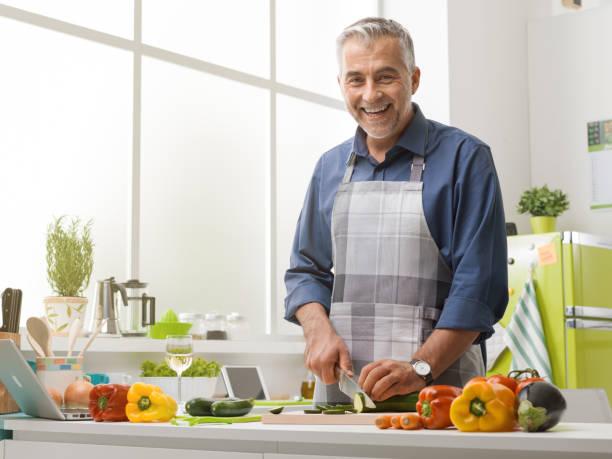 happy man cooking in the kitchen - kitchen counter imagens e fotografias de stock