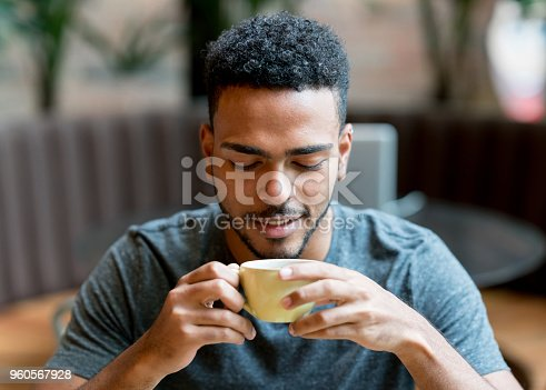 Portrait of a happy man drinking a cup of coffee at a cafe - lifestyle