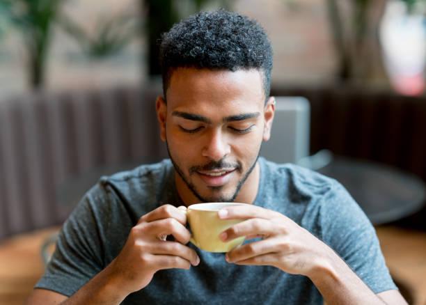 hombre feliz bebiendo una taza de café en una cafetería - café bebida fotografías e imágenes de stock