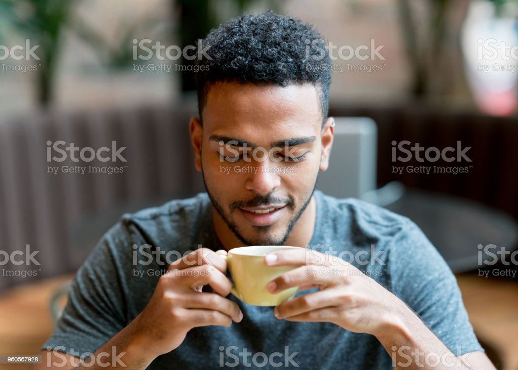 Happy man drinking a cup of coffee at a cafe stock photo