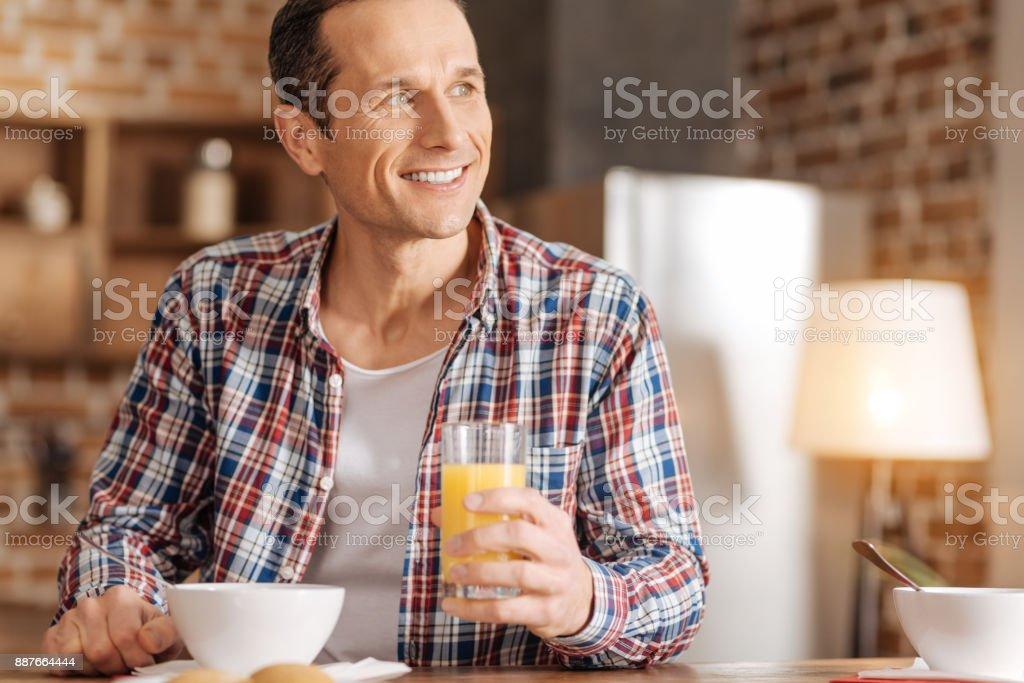 Happy man drinking orange juice at breakfast stock photo