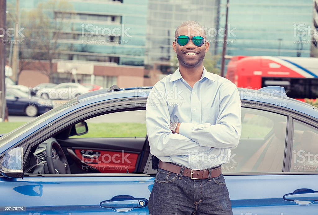 Happy man driver smiling standing by his new car stock photo
