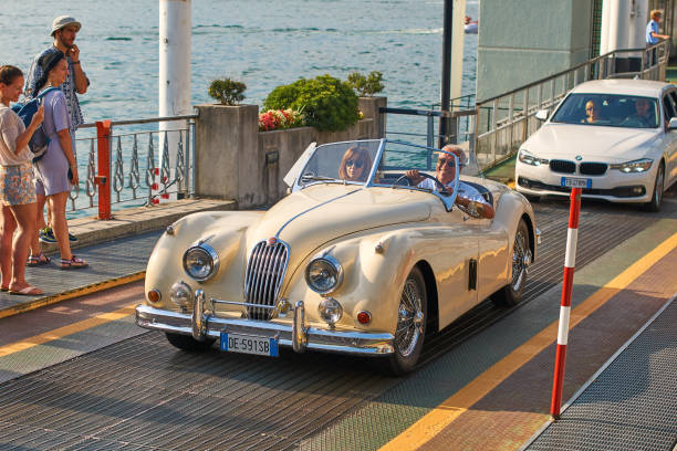 Happy man drives out his vintage beige Jaguar XK120, a sports car manufactured by Jaguar circa 1950, from the ferry boat at lake Como stock photo