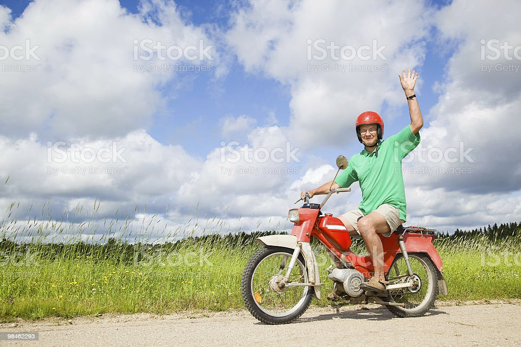 Happy man driving a moped stock photo