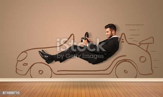 istock Happy man driving an hand drawn car on the wall 874958710