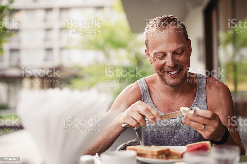 Happy man eating healthy breakfast outdoors stock photo