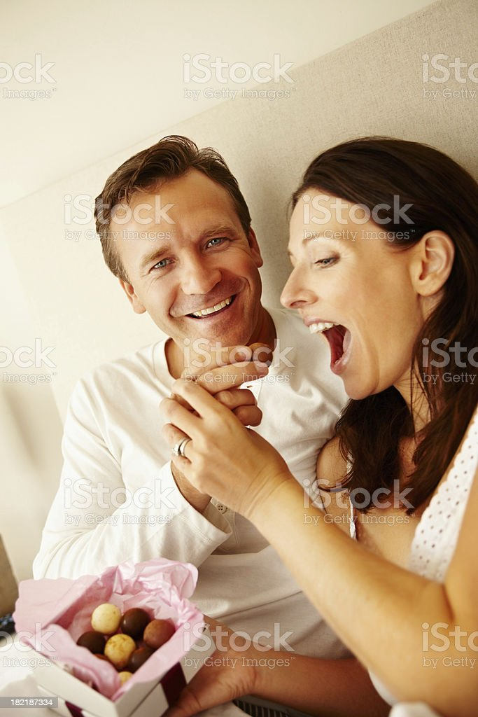 Happy man feeding sweets to his wife royalty-free stock photo