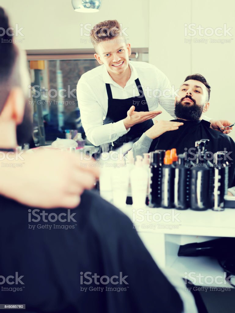 Happy man forming beard of client into shape stock photo