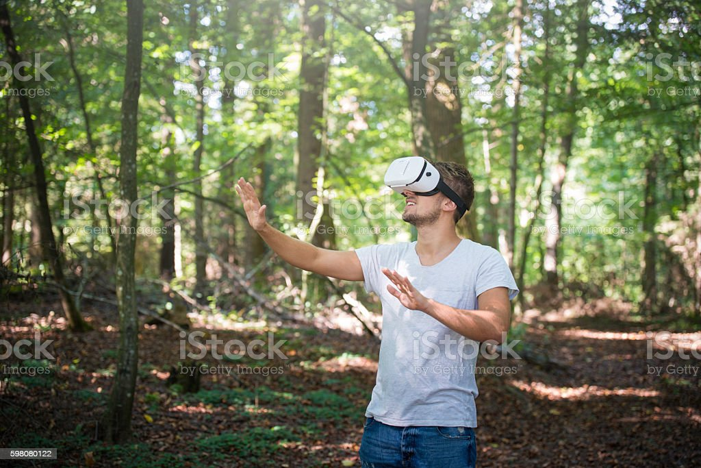 Happy man getting experience using VR-headset glasses stock photo
