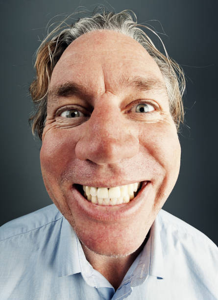 Happy man gives beaming smile, distorted by fisheye lens A mid-adult man gives a beaming, foolish, toothy smile, his face distorted by fisheye lens and wide angle. fish eye lens stock pictures, royalty-free photos & images
