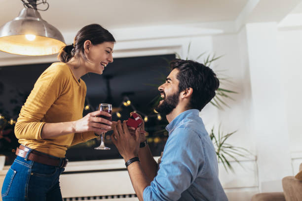 Happy man giving engagement ring in little red box to woman at home stock photo