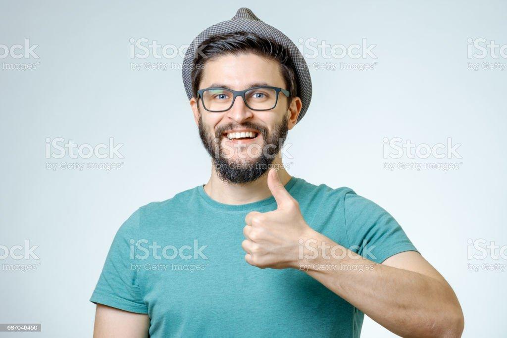 Glücklicher Mann geben Daumen nach oben Zeichen auf grauem Hintergrund Lizenzfreies stock-foto