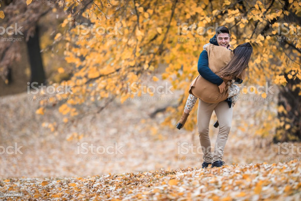 Happy man having fun with his girlfriend in the park. stock photo