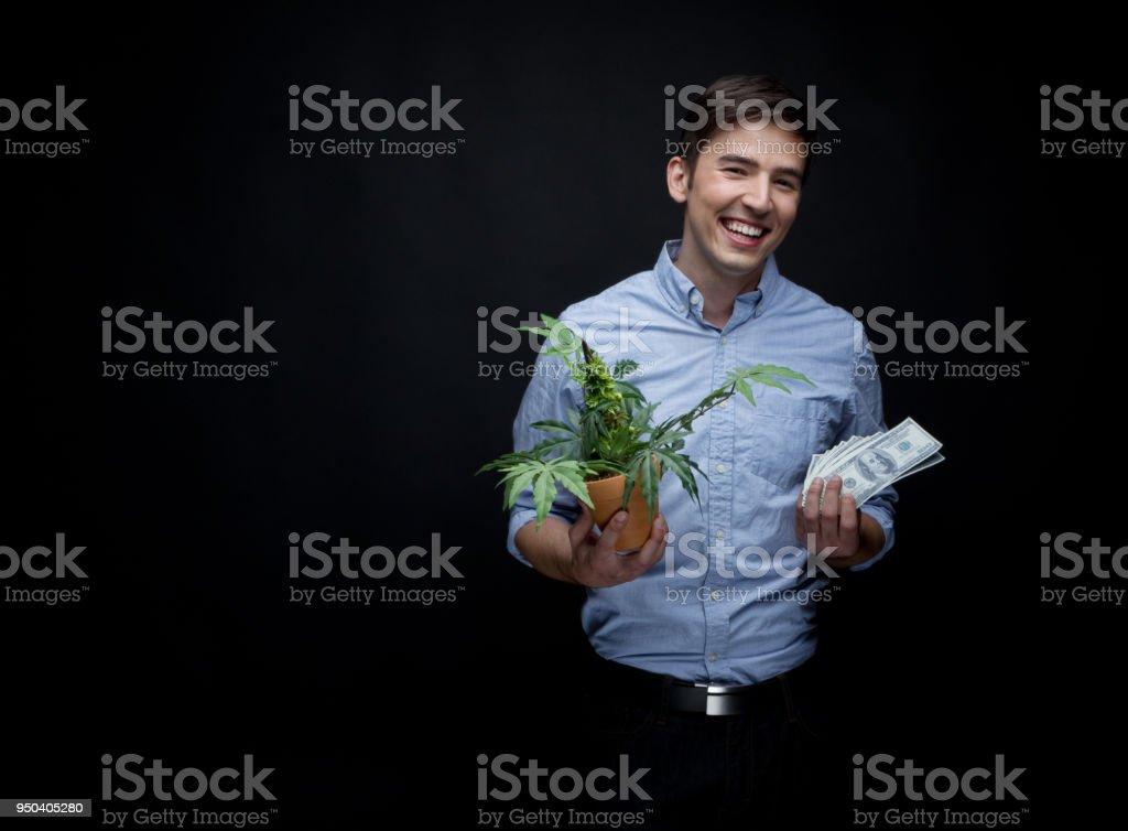 Happy man holding a marijuana plant and cash stock photo