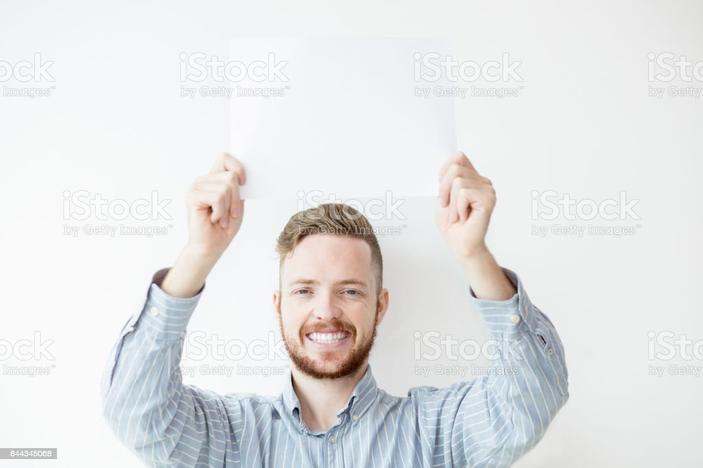 Happy Man Holding Blank Sheet of Paper Above Head stock photo