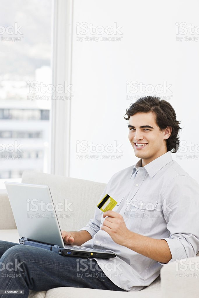 Happy man holding credit card and using laptop royalty-free stock photo