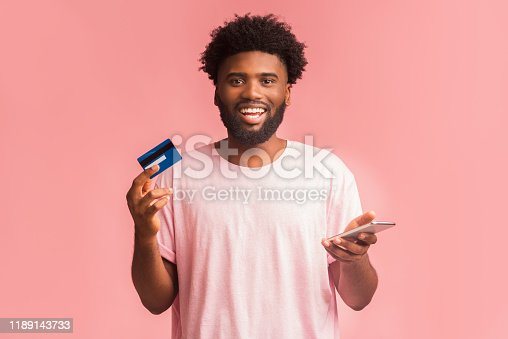 1173546354 istock photo Happy man holding credit card, using cellphone for online shopping 1189143733