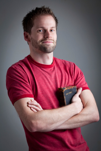 Happy man holding his old used bible