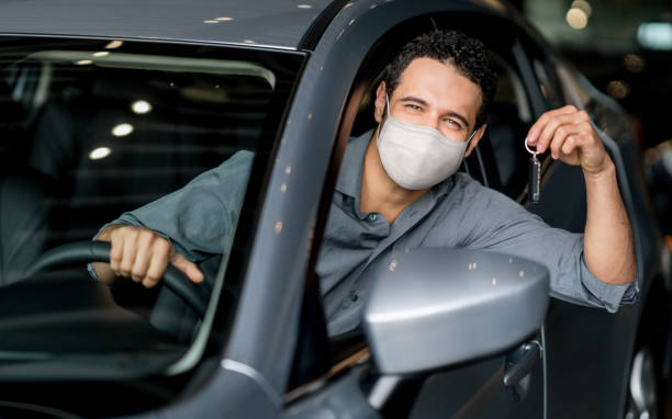 Happy man holding keys of his new car at the dealership and wearing a facemask stock photo