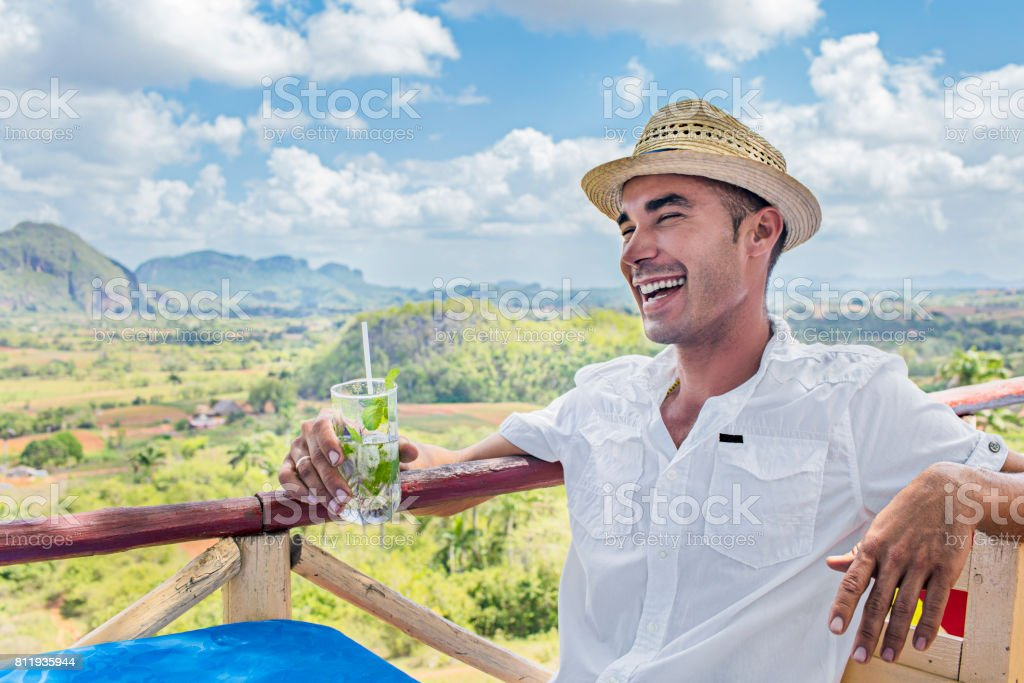 Happy man holding mojito against Valle De Vinales stock photo