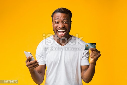 1173546354 istock photo Happy Man Holding Smartphone And Credit Card Standing, Studio Shot 1187799772