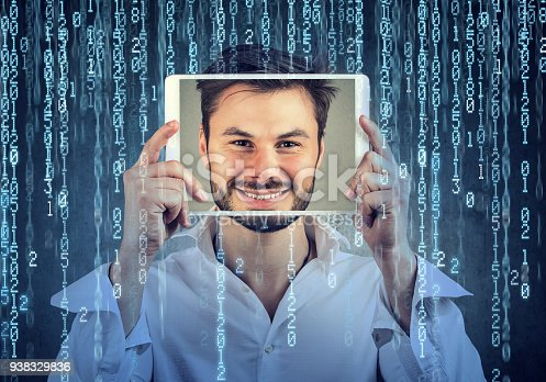 istock Happy man holding tablet with his face displayed on a screen on binary code background 938329836