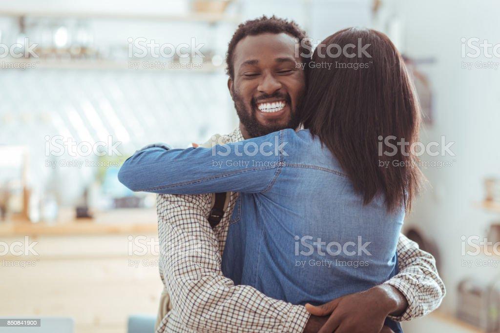 Glücklicher Mann umarmt seinen besten Freund im Kaffeehaus – Foto