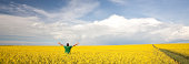 A happy man lifts his arms in a canola field. Rural scenic. Wide angle.