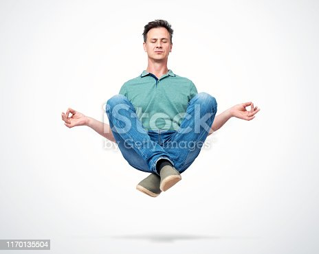 Happy man in casual clothes closing his eyes meditating levitating in the air. Comprehended relaxation