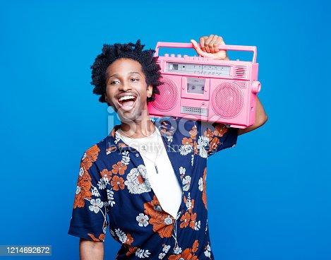 istock Happy man in hawaiian shirt holding pink boom box 1214692672