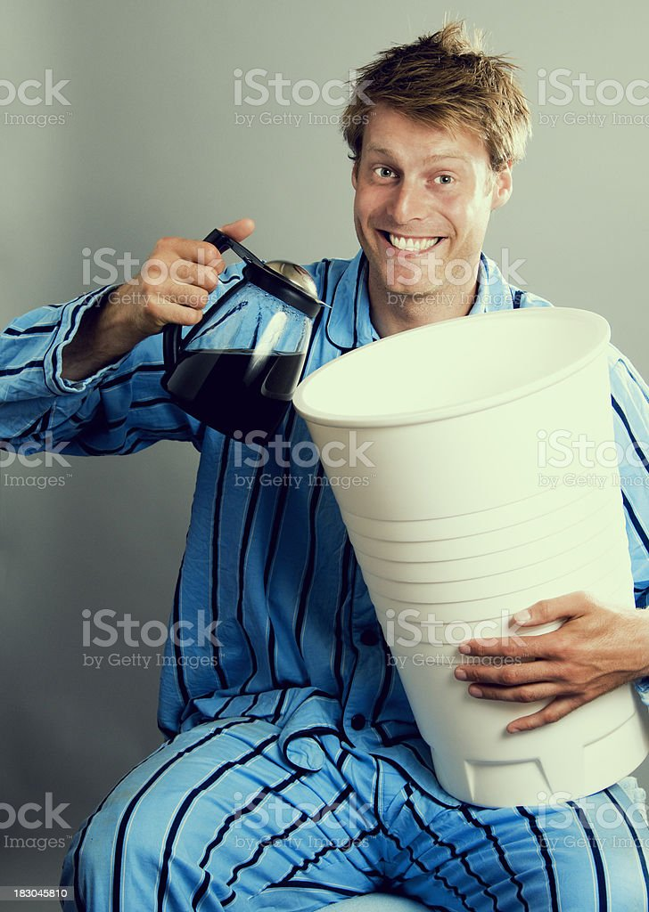Happy man in pajamas holding giant coffee cup royalty-free stock photo