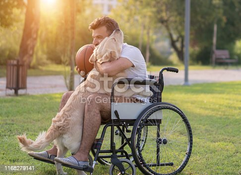 Happy Man in wheelchairs is playing with her dog