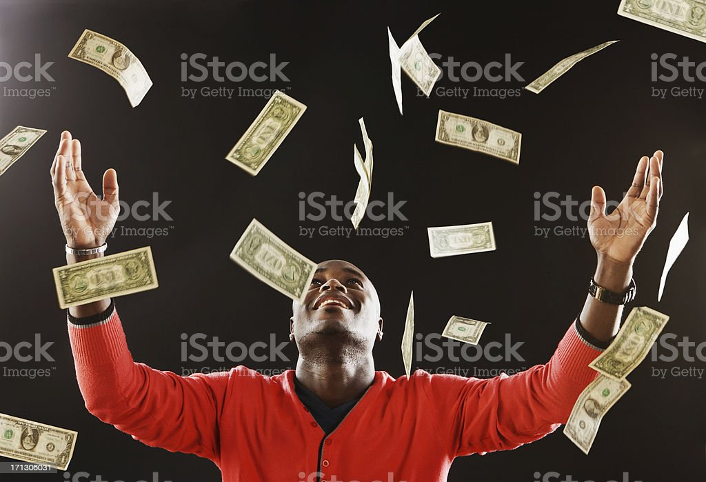 Happy man is showered in dollar bills stock photo