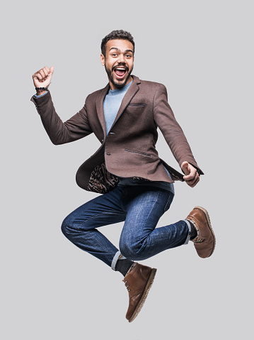 Excited laughing young man is jumping, isolated on grey background
