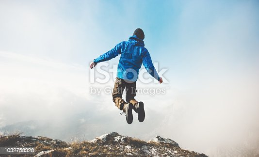 istock Happy Man jumping on mountains cliff to clouds sky Lifestyle Travel emotional success concept adventure active vacations outdoor 1032758328