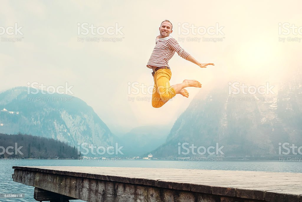 Happy man jumps on wooden pier at the mountain lake stock photo