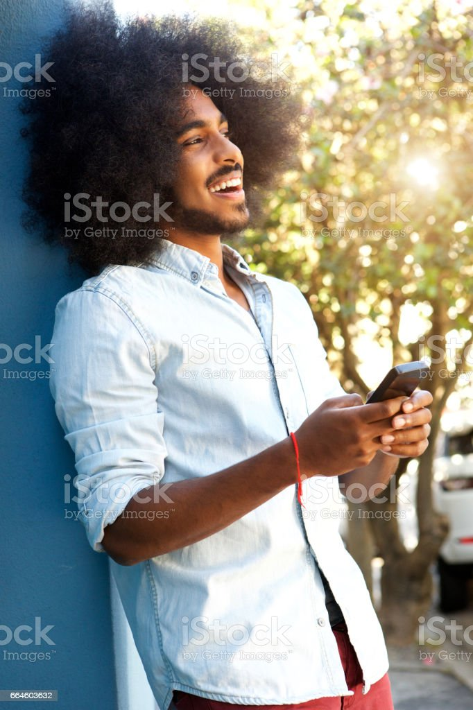 happy man leaning against wall with mobile phone stock photo