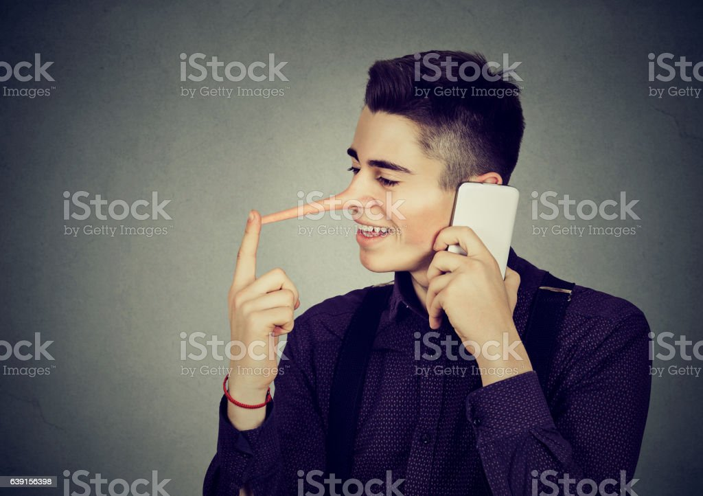 Happy man liar with long nose talking on mobile phone stock photo