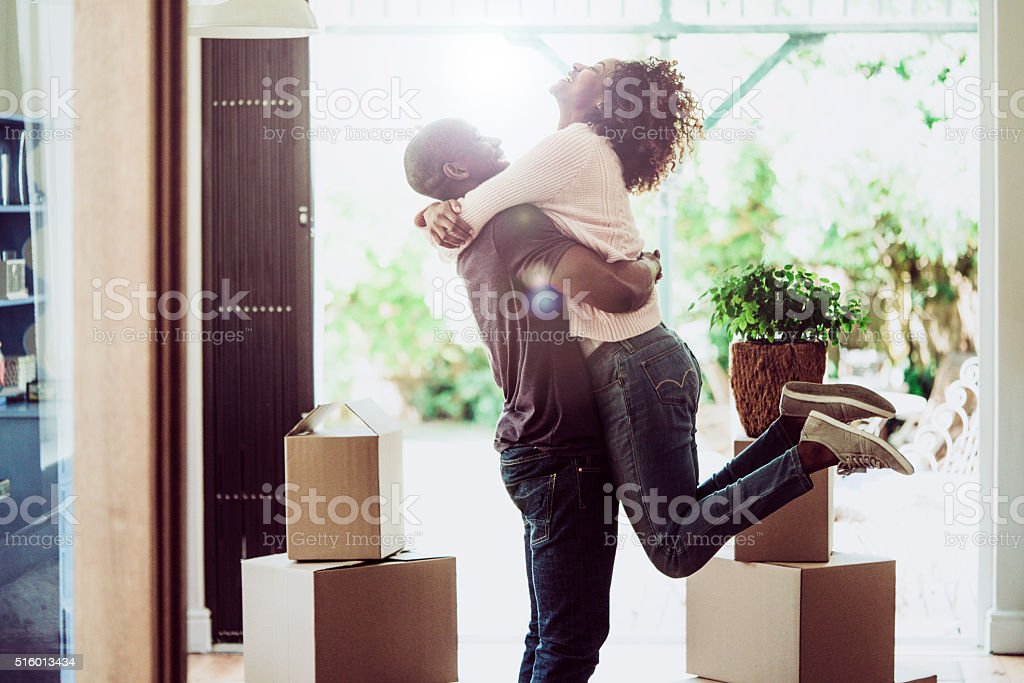Happy man lifting woman in new house​​​ foto