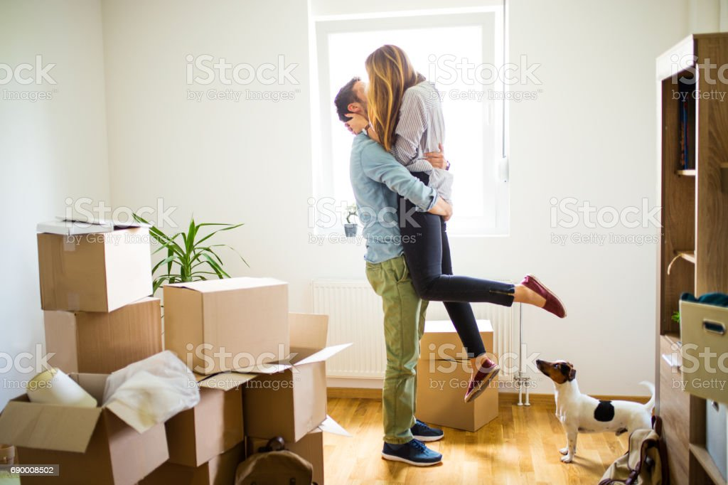 Happy man lifting woman in new house stock photo