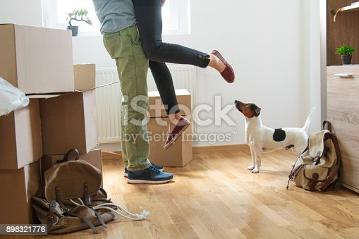 istock Happy man lifting woman in new house 898321776