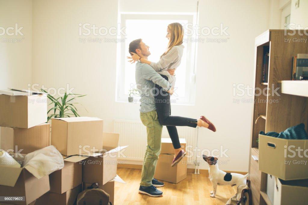 Heureux homme levant femme dans la nouvelle maison - Photo