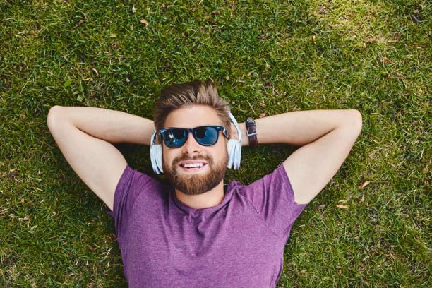 Glücklicher Mann lauscht Musik, die auf Gras im Park liegt. – Foto