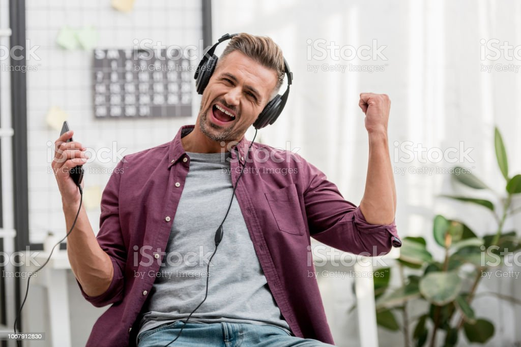 happy man listening music and singing while sitting on chair