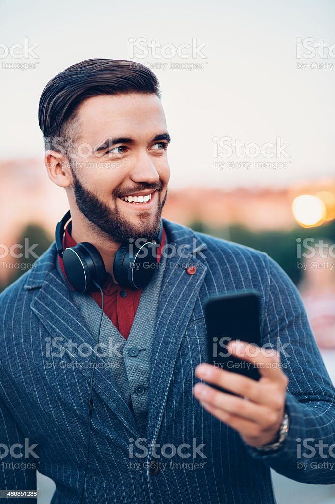 Young man with headphones and smart phone at urban scene